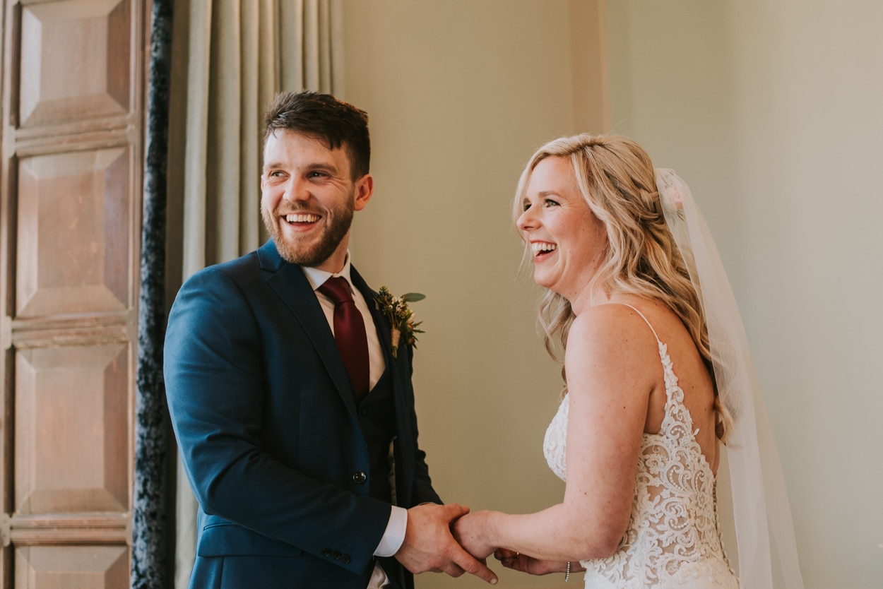 bride and groom facing each other holding hands and laughing