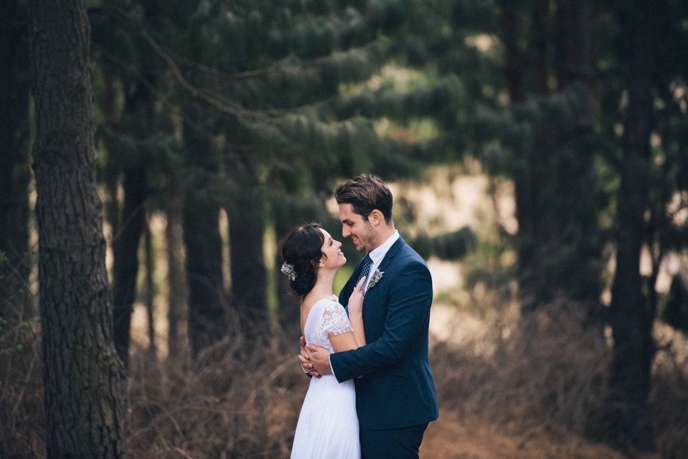 bride and groom hugging infront of a forest of trees
