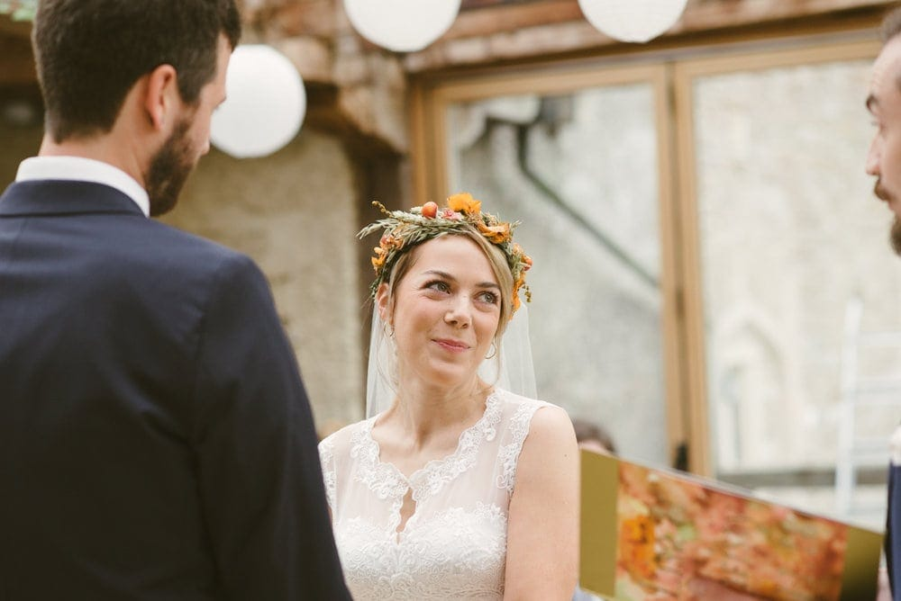 Blonde bride with flowers in her looking at her groom smiling