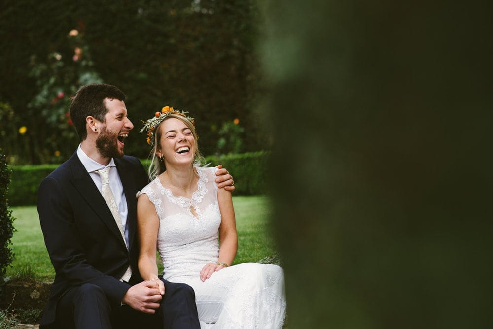 Bride and groom couple sitting and laughing in gardens