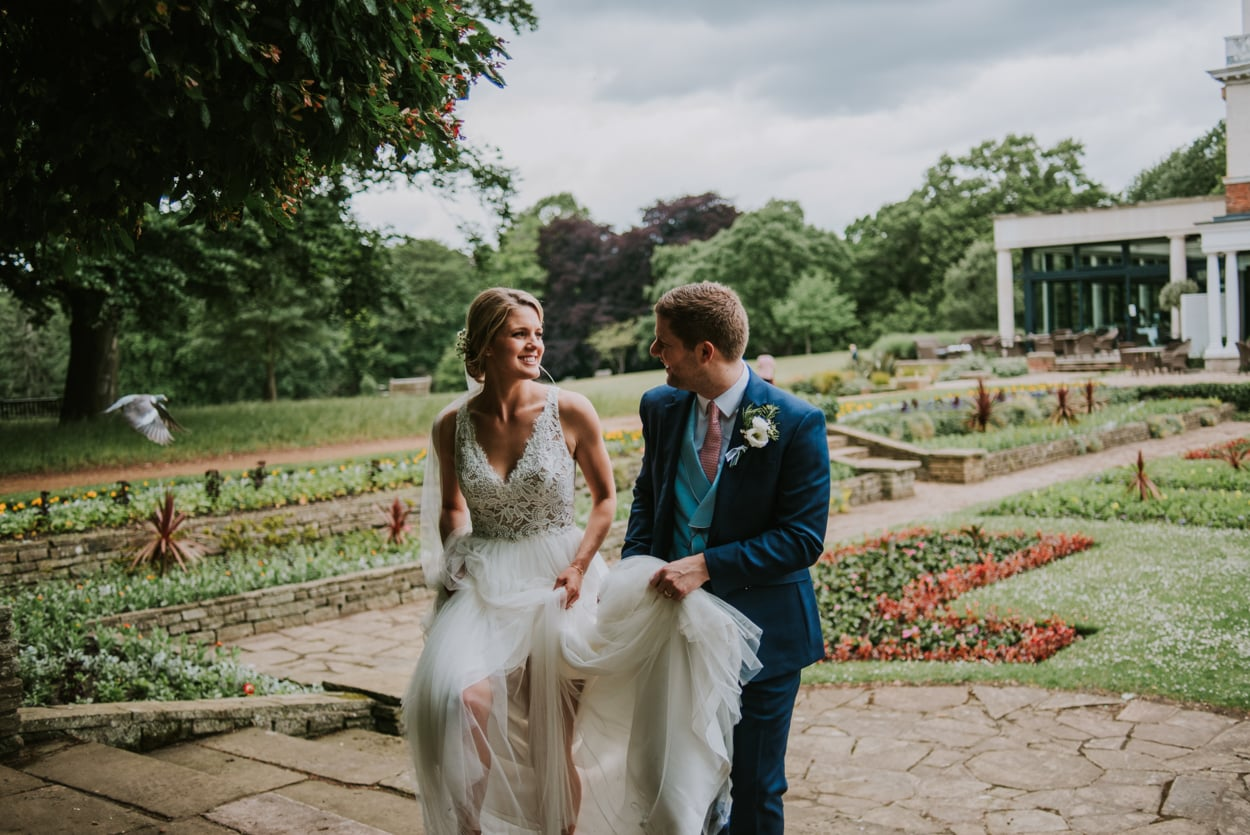 A groom holding a bride's dress as they walk through gardens