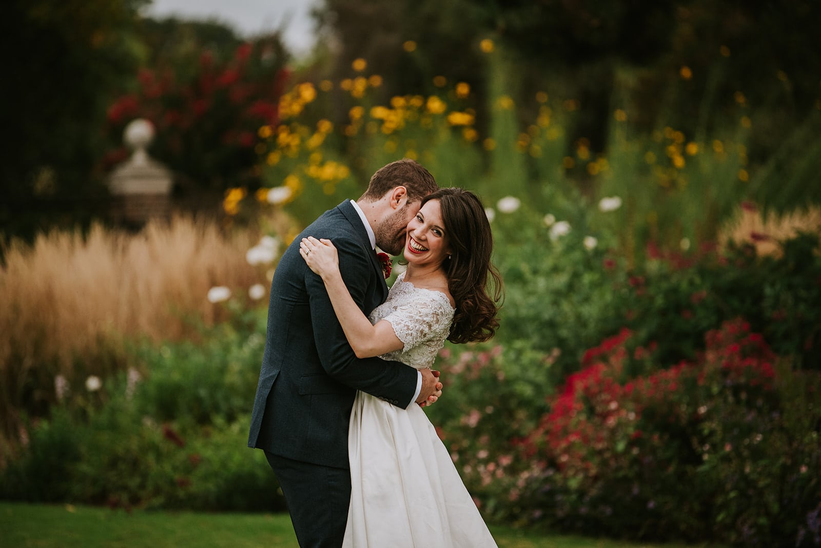 Bride and groom hugging surrounded by colourful flowers in a garden