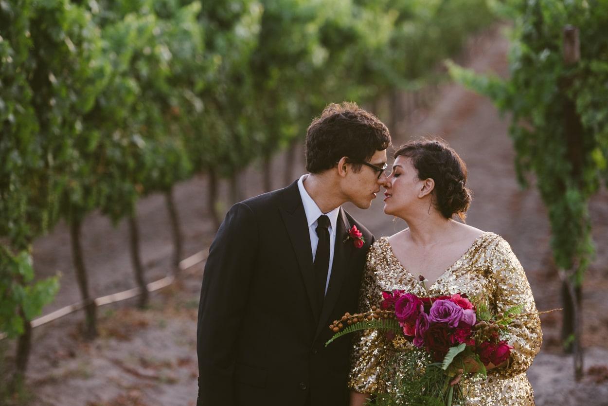bride and groom standing in vineyards