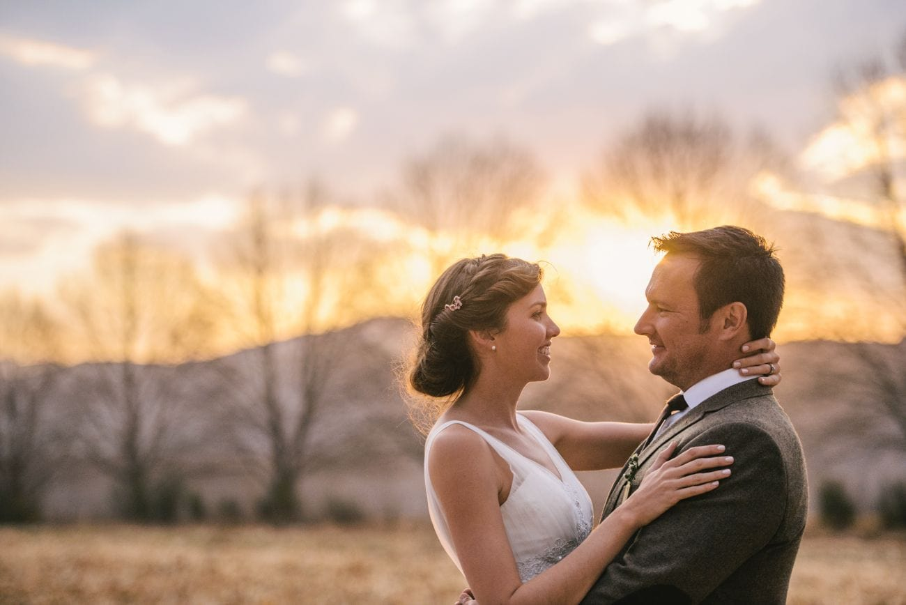 bride and groom looking at each other standing in front of a sunset outdoors