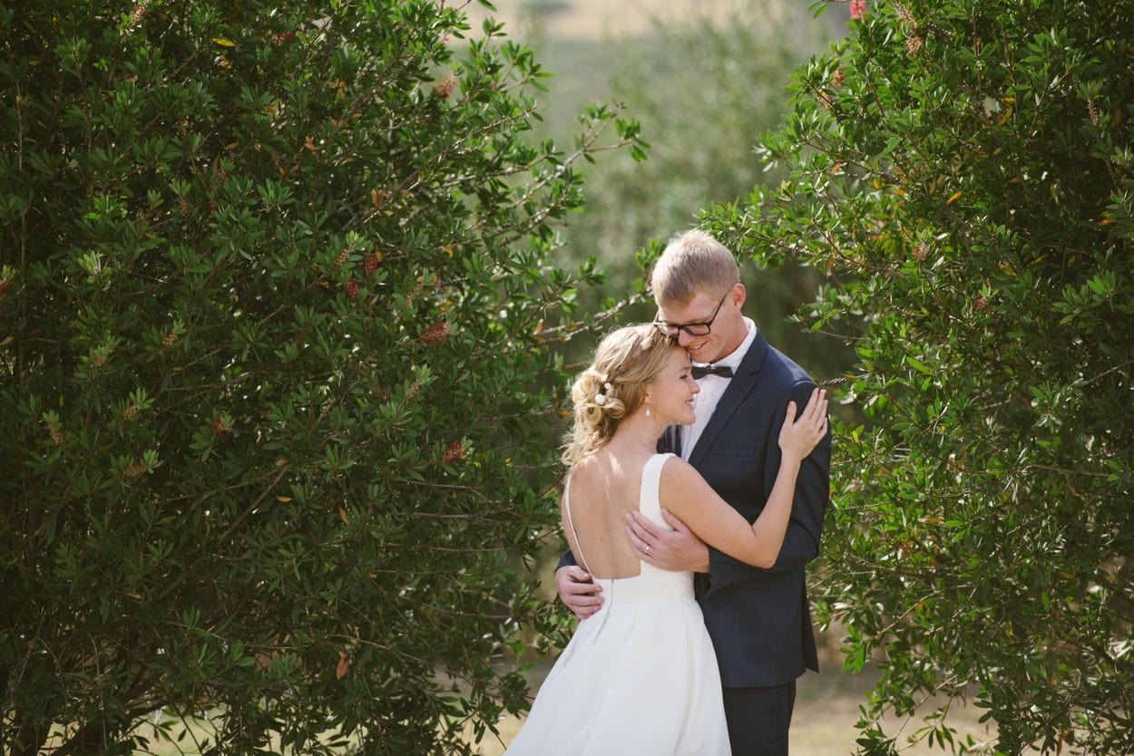 bride and groom hugging in an orchard
